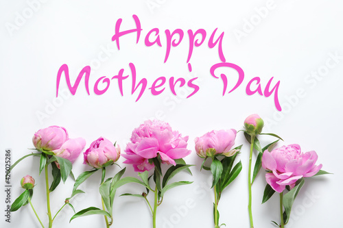 Happy Mother's Day. Beautiful peonies on white background, flat lay