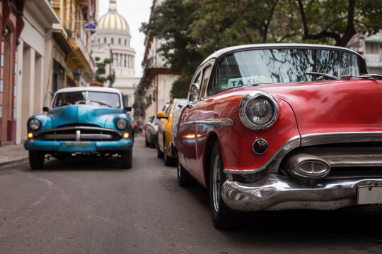 Old car on streets of Havana with colourful buildings in background. Cuba