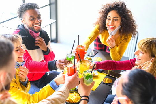 Multicultural  young friends toast and drinking cocktail with open face mask - New normal lifestyle concept with millennials having fun together talking at cocktail bar