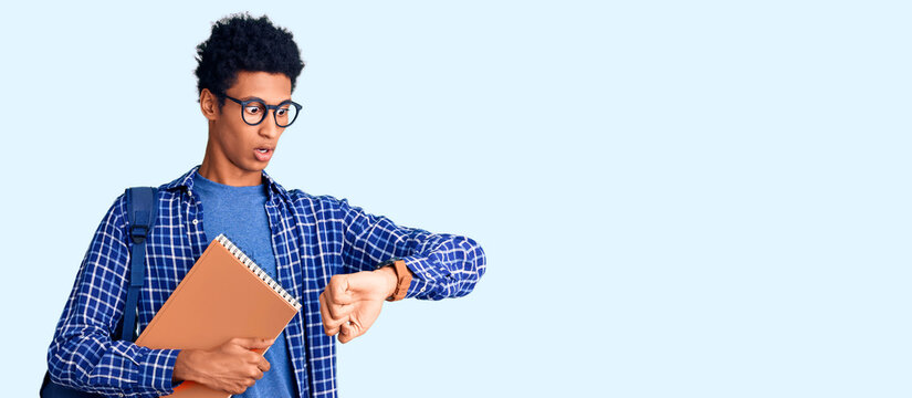 Young african american man wearing student backpack holding book looking at the watch time worried, afraid of getting late