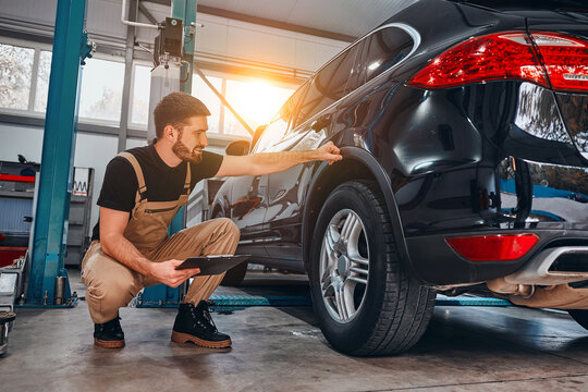 Handsome mechanic in uniform is making notes examining car in auto service.