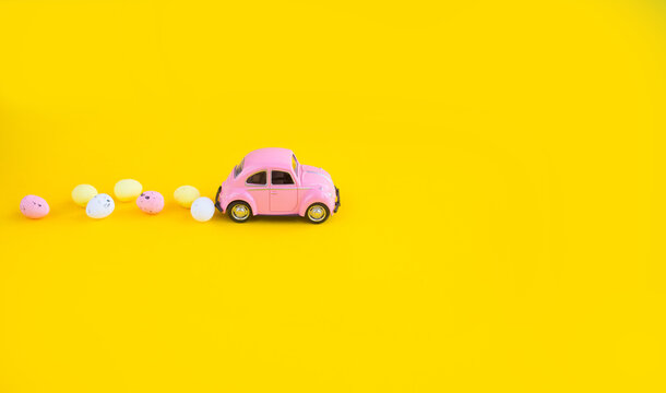 Kiev, Ukraine-March 13, 2021:  Retro toy pink car with Easter egg on the roof. Easter card with space for text on a yellow background. Easter grocery delivery.