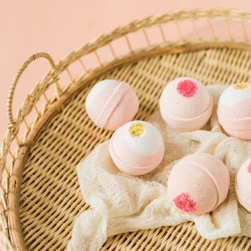 Group of pink and white bath bombs in woven tray on pink background