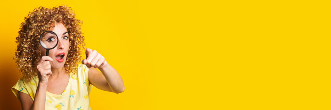 surprised young woman pointing her finger looks through a magnifying glass on a yellow background. Banner.