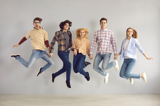 Full-length studio portrait of enthusiastic caucasian european teenager jumping high rejoicing start of holidays, end of academic year or quarantine, getting education grant or admission to university