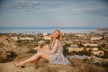 A young blonde girl in a gray dress sits on a hilltop overlooking the seaside town of Feodosia in Crimea in summer Wall mural