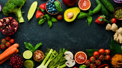 Food. Set of fresh vegetables and fruits on a black stone background. Organic food. Top view. Free space for your text.
