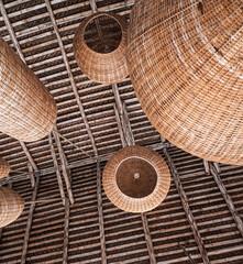 Tropikalne lampy wiklinowe, naturalne ekologiczne budownictwo, widok na dach z belek drewna.