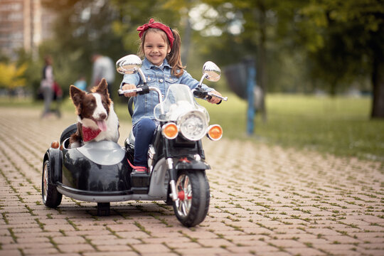 cute little girl  driving electrical motorcycle toy with sidecar and her dog in it.