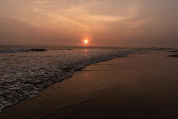 Krajobraz zachodu słońca nad brzegiem oceanu, plaża i nastrojowy widok.