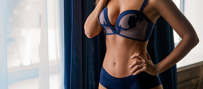 beautiful slender woman in lingerie on the background of the window posing