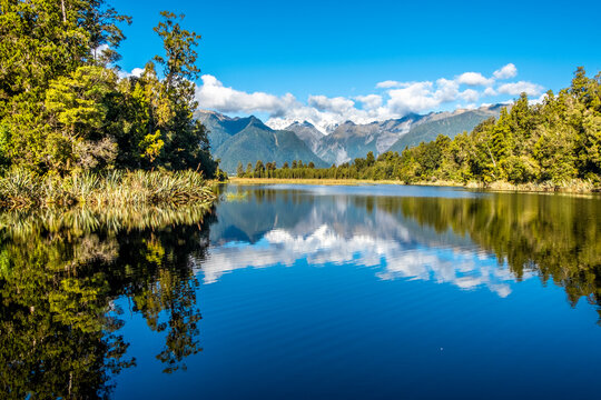 The Southern Alps reflecting in Matheson Lake. South Island, New Zealand.