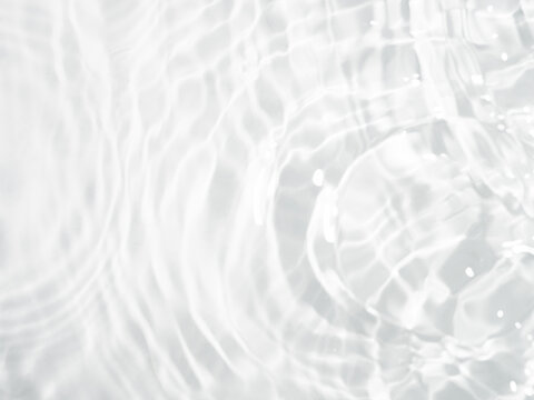 Blurred ripple water texture on white background. Shadow of water on sunlight. Mockup for product, spa or travel background. Marble water surface as wallpaper background