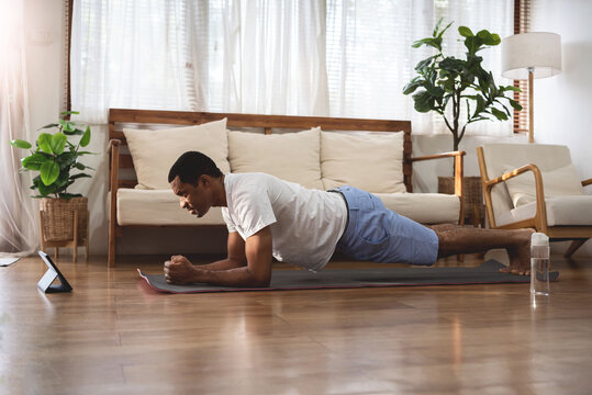 Side view of Black African American man looking at digital tablet and doing plank exercise at home. Wellness, Fitness and healthy lifestyle.