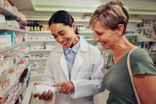 Smiling senior customer with pharmacist looking for medicinal details on bottle standing near shelves