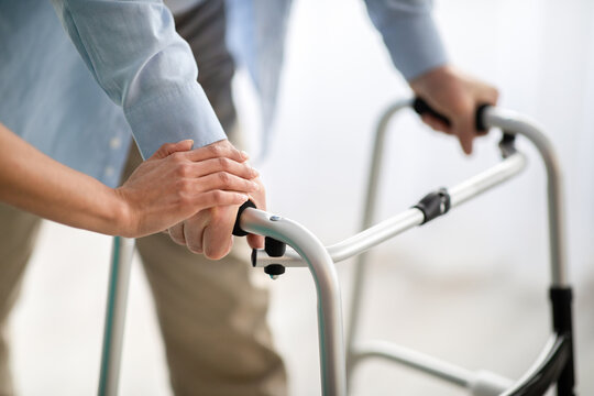 Unrecognizable elderly man using walker, young doctor supporting and helping him at retirement home