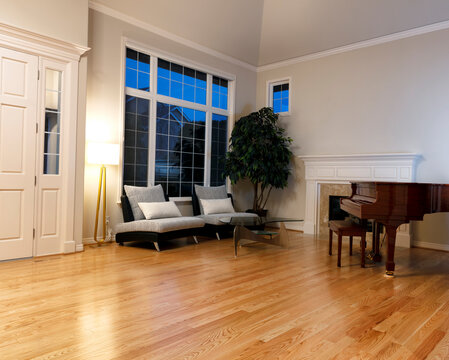 Modern living room with real oak hardwood floors, piano, fireplace and large windows during late evening