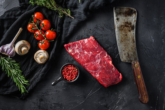 Raw, flap or flank, also known Bavette steak near butcher knife with pink pepper and rosemary. Black background. Top view