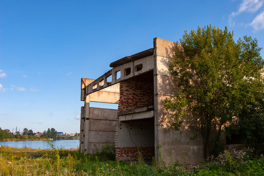 Abandoned panel building. Industrial building is abandoned. It is overgrown with grass and trees. Concept - abandoned building of a decayed factory. He is missing windows and part of walls