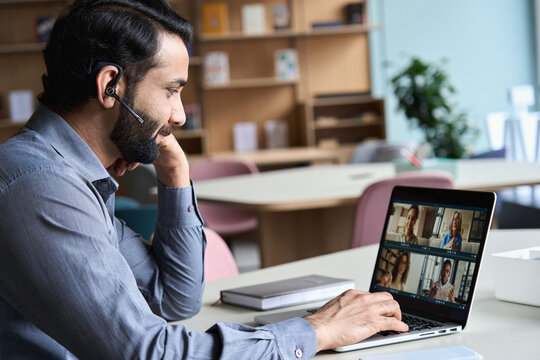 Indian business man wearing headset having virtual team meeting on video conference call, using laptop work from home office talking to diverse people group in remote teamwork online distance chat.