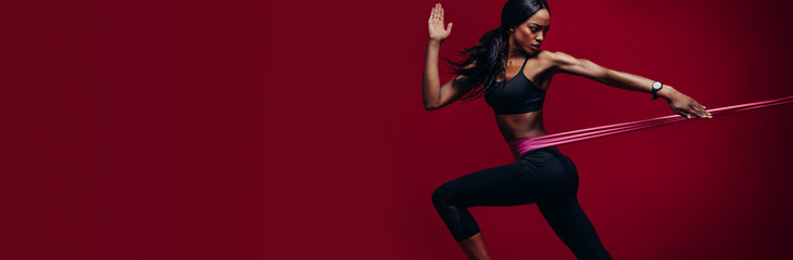 Strong woman exercising with a resistance band - fototapety na wymiar