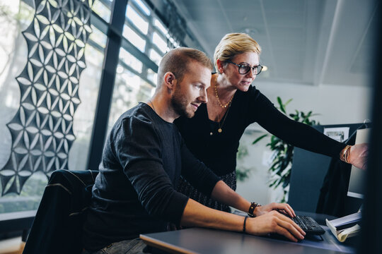 Manager assisting colleague working in office
