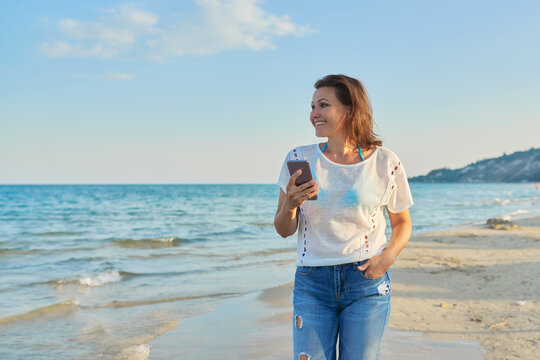 Middle-aged woman walking along beach with smartphone
