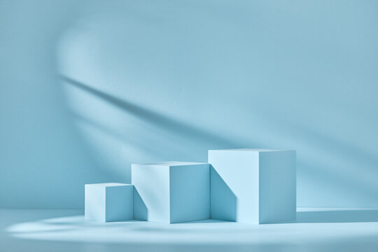 Blue background for product presentation with shadows and light. Empty podiums. Mockup.
