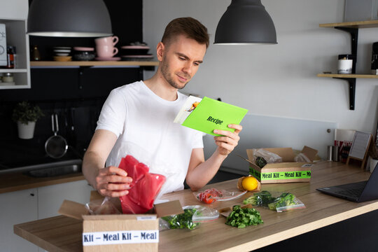 Happy Caucasian white man Unpack Online Home Food Delivery. Box with packed tuna, shrimp, vegetables and recipe card on a kitchen background. Food delivery services. Dinner Set from restaurant