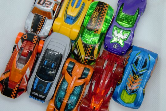 Mix of miniature, colorful toy cars. A lot of little toy car models, ready for play. Toy cars background, top view. Warsaw, Poland - March 3 2021