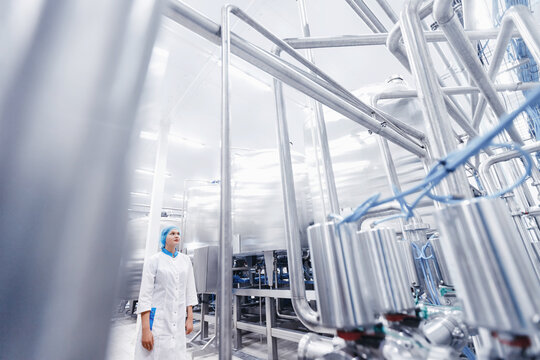 Industrial portrait operator female in uniform background food factory production line
