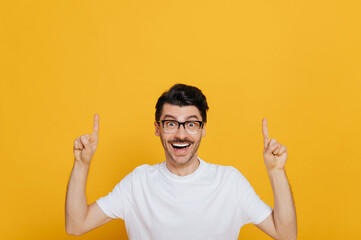 Fototapeta Handsome caucasian cheerful young man in white basic t-shirt and glasses amazed looks at the camera and points fingers up at empty space, stands on isolated orange color background obraz