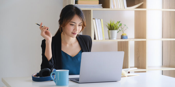 Businesswoman in having a video call on laptop while discussion with business partner during work from home.