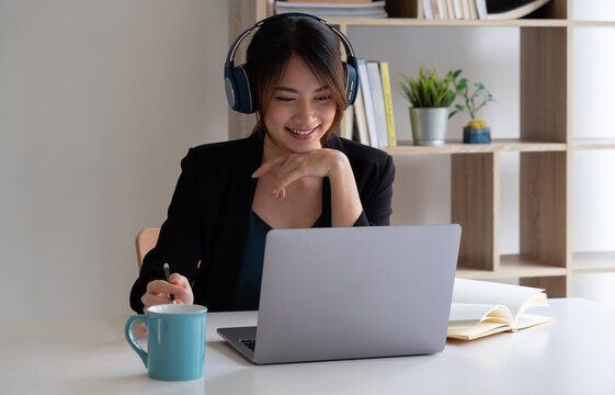 Happy asian woman wear headset laugh using laptop video stream conference call teach online, happy ethnic girl student gamer tutor have fun watch webinar web cam education entertainment concept