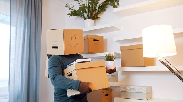 Happy young man with smiling cardboard box over his head dancing while moving in the new home. High quality photo