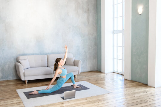 Woman doing spot practicing yoga stretching from home using laptop and internet