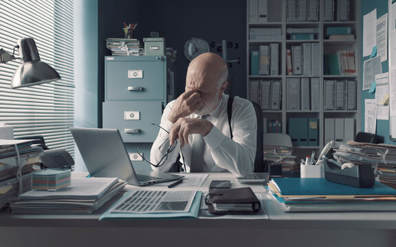 Tired stressed office worker rubbing his eyes
