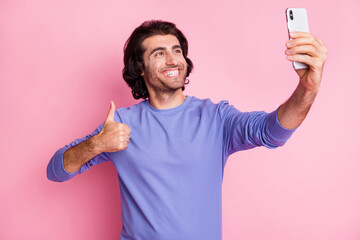 Photo of optimistic guy doing selfie show approve sign wear purple sweater isolated on pastel pink color background