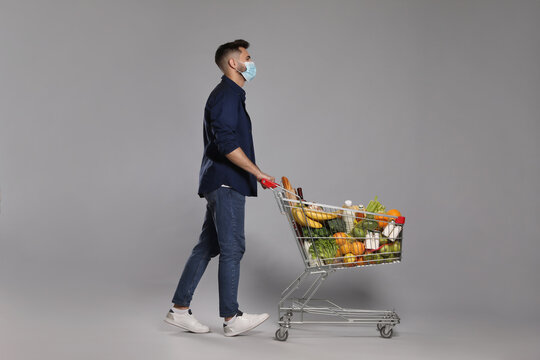 Man with protective mask and shopping cart full of groceries on light grey background