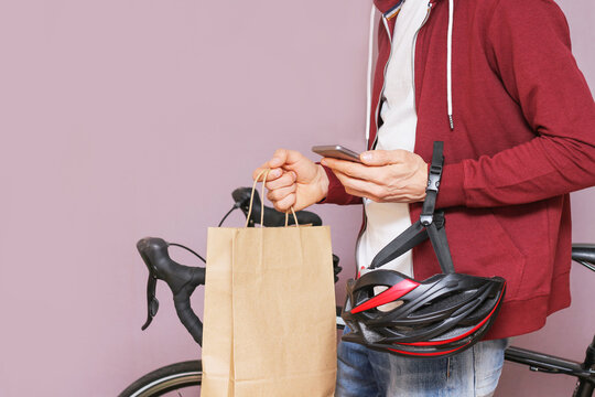 Male courier with bicycle and smartphone. Delivery food service Studio shot Copy space