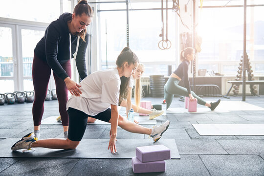 Professional gym coach guiding women with stretching