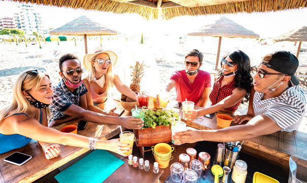 Young trendy people toasting at beach cocktail bar chiringuito with open mask - New normal summer life style concept with friends having fun together cheering drinks - Warm bright backlight filter