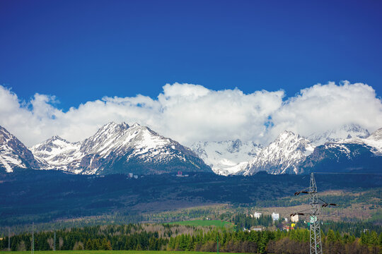 high tatra mountain ridge in springtime. cloud above the snow capped rocky peaks. beautiful sunny weather. wonderful nature scenery
