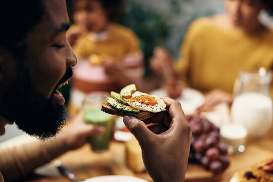 Close-up of black  man eating healthy sandwich at home.