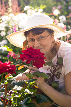Positive smiling senior woman in a white hat with a wide brim smelling beautiful red roses in a summer garden