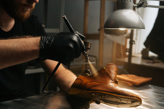 Close-up hands of unrecognizable shoemaker wearing black gloves spraying paint of light brown leather shoes. Concept of cobbler artisan repairing and restoration work in shoe repair shop.