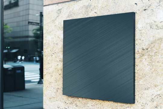 Black square sign with blank space for your logo on the marble wall of a modern shopping mall, mock up