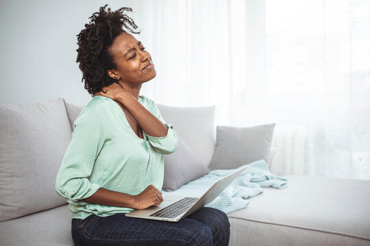 African young woman have neck ache during working with laptop at home. Young Businesswoman Suffering From Neckache. Woman having neck pain while working on computer laptop