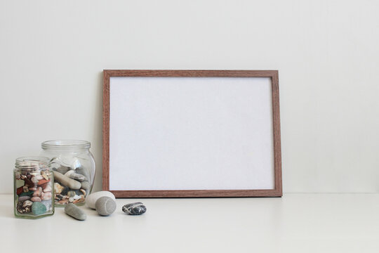 wooden frame and sea stones in a jar on the table