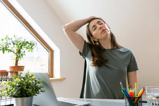 Beautiful women exercising at home office by stretching her neck. Healthy living and body care while at home.